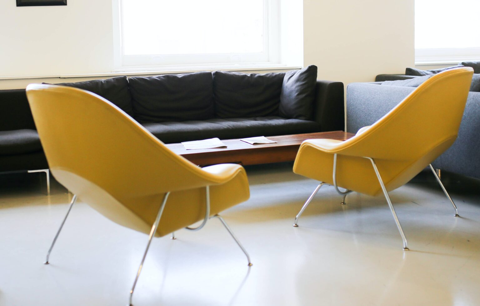 Yellow chairs and black couch living space