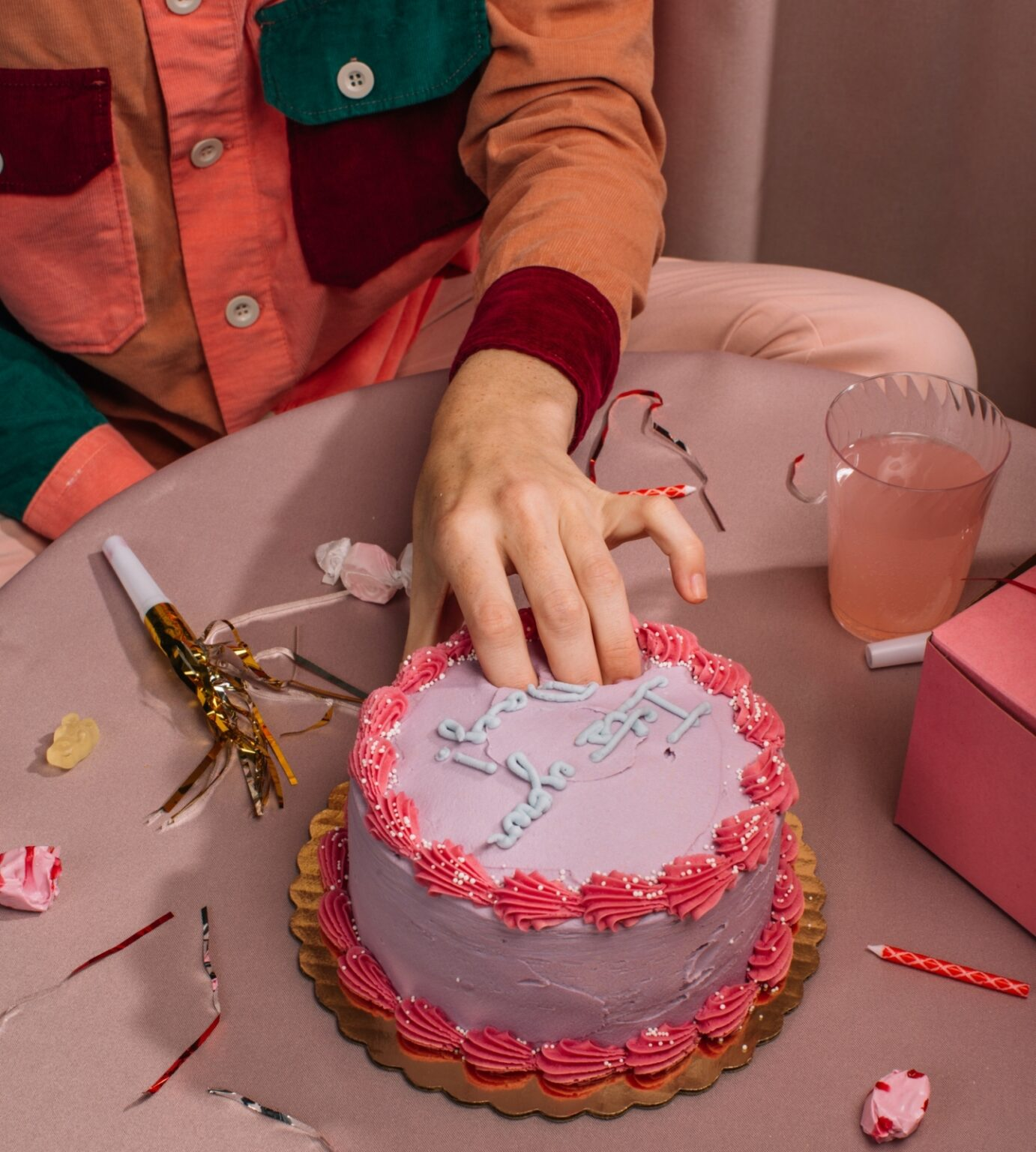 Fingers in pink birthday cake food porn