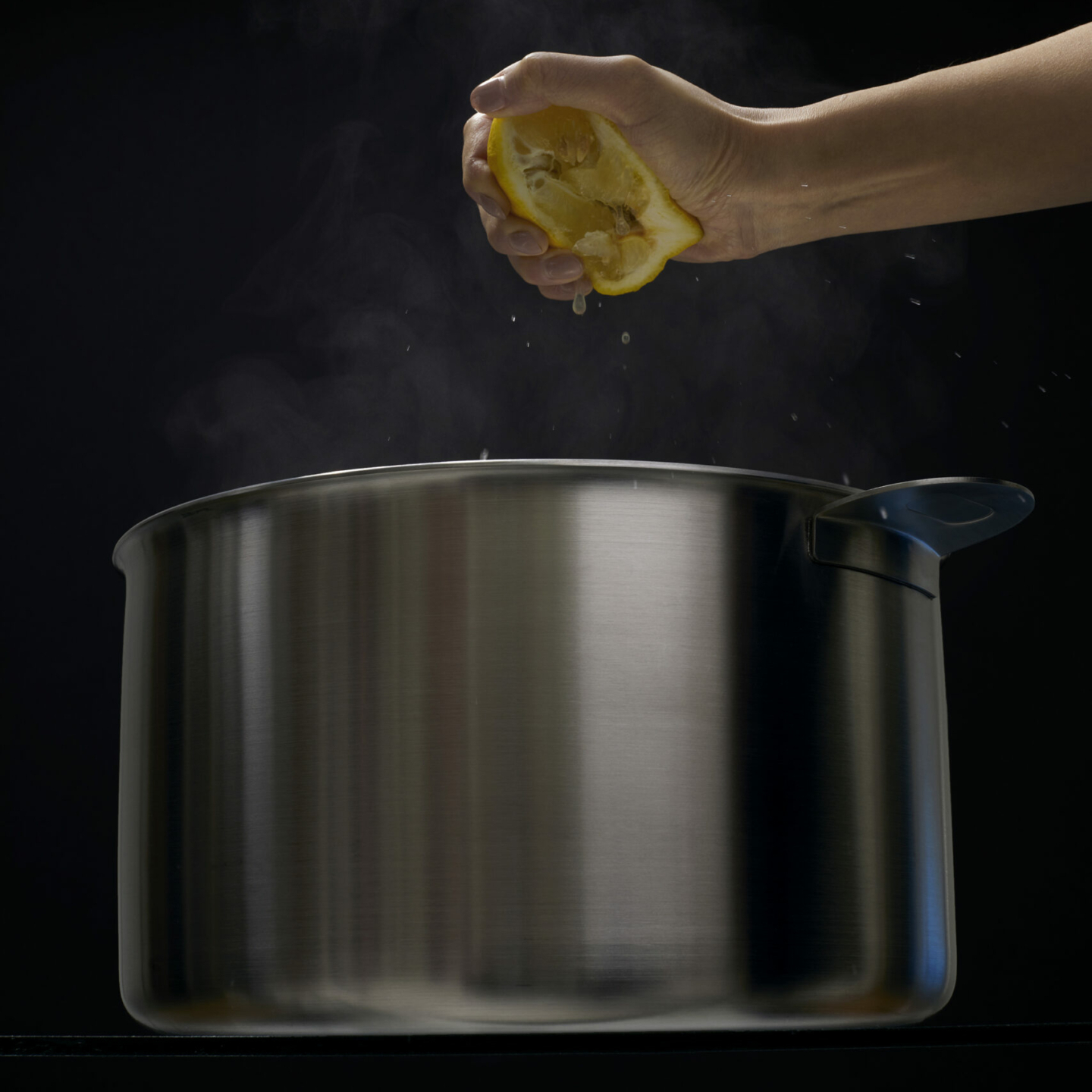 Hand squeezing lemon over stackware stockpot