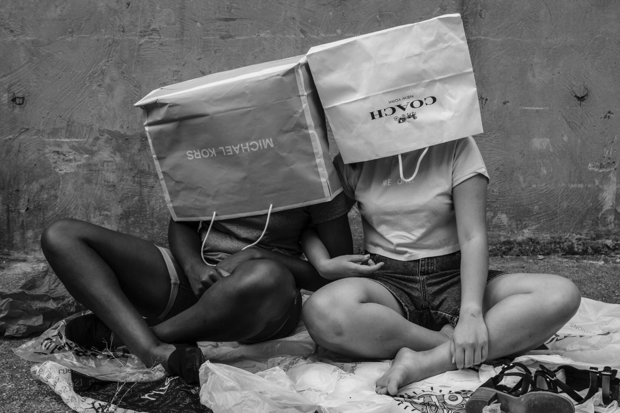 black and white girls with shopping bags on their heads consumerism too much buying