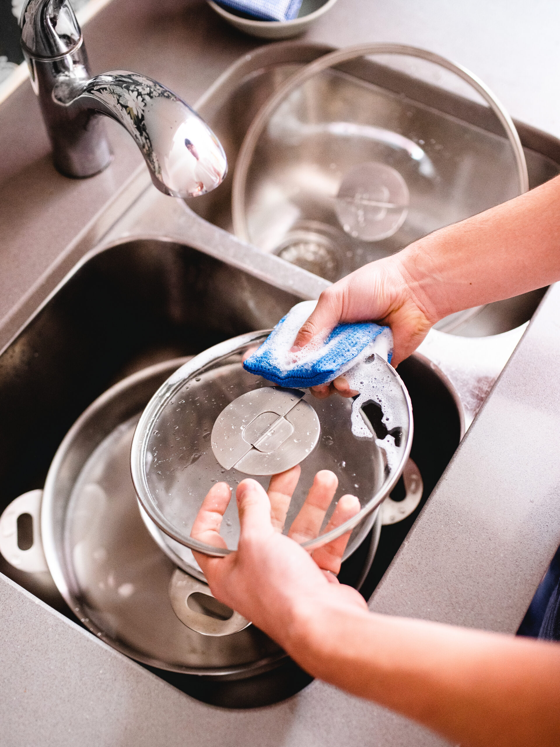 Hands cleaning stackware glass lids in sink