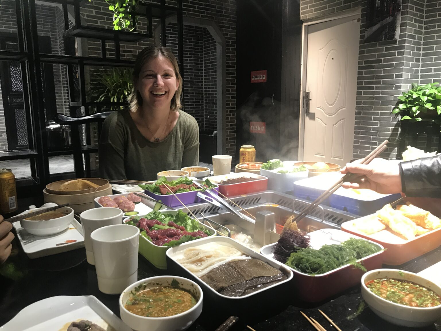 Woman sitting at crowded table with food Shanghai