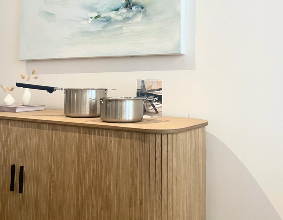 Stainless steel cookware on wooden midcentury cabinet